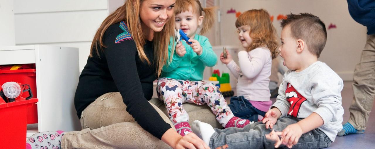 medewerker van een kinderdagverblijf met 3 peuters